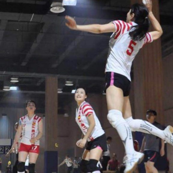Red White Volleyball sublimation uniform in play women jumping